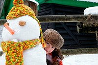 Woman hiding behind snowman