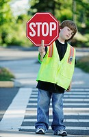 Portrait of boy holding stop sign