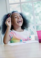 Girl laughing and painting