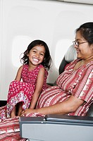 Portrait of young daughter sitting on mother's lap on airplane (thumbnail)