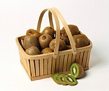 Kiwi fruits in basket with handle, one cut open in front
