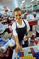 Portrait of a female sales clerk working on a cash register at a supermarket checkout counter