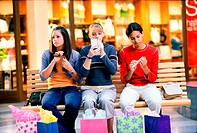 Three teenage girls sitting on a bench in a shopping mall applying make-up