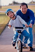 Portrait of a father helping his son ride a bicycle