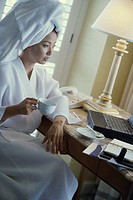 Young woman wearing a bathrobe holding a cup of coffee and looking at a laptop in a hotel room