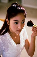Young woman applying make-up with a brush