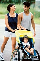 Parents walking with their baby girl in a stroller