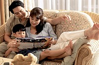 Parents with their son reading a book