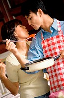 Young man holding a pan and spatula kissing a young woman in the kitchen