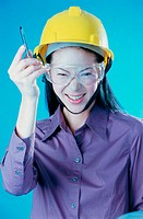 Portrait of a construction worker wearing a hardhat holding a pen
