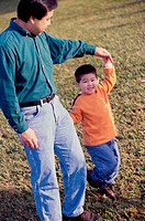 Father and son holding hands walking together in the park