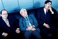 Three businessmen sitting on a couch in an office