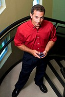 Portrait of a businessman standing on stairs holding a mobile phone