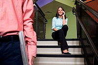 Portrait of a businesswoman sitting on stairs talking on a mobile phone