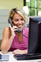 Businesswoman sitting in front of a computer talking on a telephone