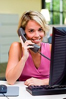 Portrait of a businesswoman sitting in front of a computer talking on a telephone
