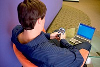 High angle view of a businessman sitting in front of a laptop holding a palmtop
