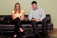 Businessman and a businesswoman sitting on a couch holding mobile phones