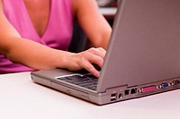 Mid section view of a businesswoman working on a laptop