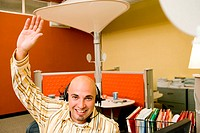 Portrait of a male customer service representative wearing a headset with his hand raised