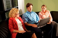 Two businesswomen and a businessman sitting on a couch in front of a laptop