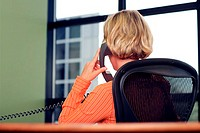 Rear view of a businesswoman sitting in an office talking on a telephone
