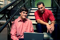 Portrait of two businessmen sitting on stairs in front of a laptop