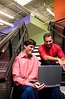 Two businessmen sitting on stairs in front of a laptop