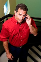 Portrait of a businessman standing on stairs talking on a mobile phone