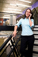 Portrait of a businesswoman standing on stairs talking on a mobile phone