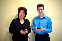 Portrait of a businesswoman and a businessman standing in an office holding a palmtop and a mobile phone
