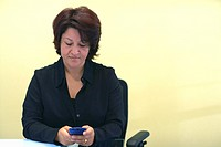 Businesswoman sitting in an office working on a palmtop