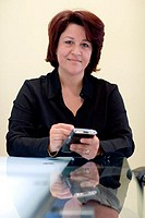 Portrait of a businesswoman sitting in an office working on a palmtop