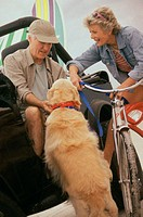 Senior couple on a jeep and bicycle with their dog