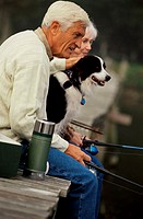 Side profile of a senior couple fishing on a pier with their dog