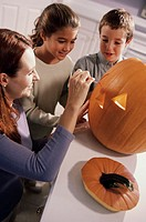 Mother carving a pumpkin with her son and daughter (thumbnail)