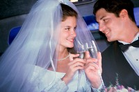 Newlywed couple toasting with champagne glasses in a car