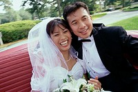 Newlywed couple sitting in a convertible car