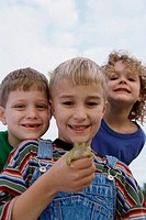 Low angle view of a boy standing with his friends holding a frog