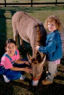 Portrait of two girls petting a donkey
