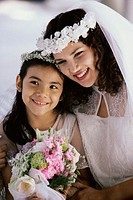 Close-up of a bride smiling with a flower girl