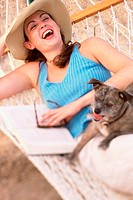 Young woman lying in a hammock with her dog