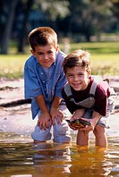 Portrait of two boys standing in water holding a turtle