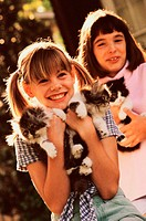 Two girls holding kittens