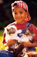 Portrait of a boy holding cats