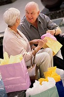 Senior couple sitting together looking into shopping bags
