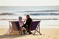 Senior couple holding glasses of champagne on the beach