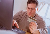 Young man sitting in front of a laptop holding a credit card
