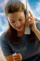Young woman using a cordless phone holding a credit card