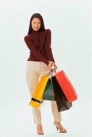 Portrait of a young woman carrying shopping bags
